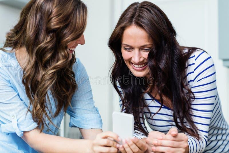 Le kvinnliga vänner som använder mobiltelefonen arkivbild