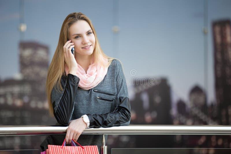 Le kvinnlign i shoppinggalleria som talar på smartphonen royaltyfria foton