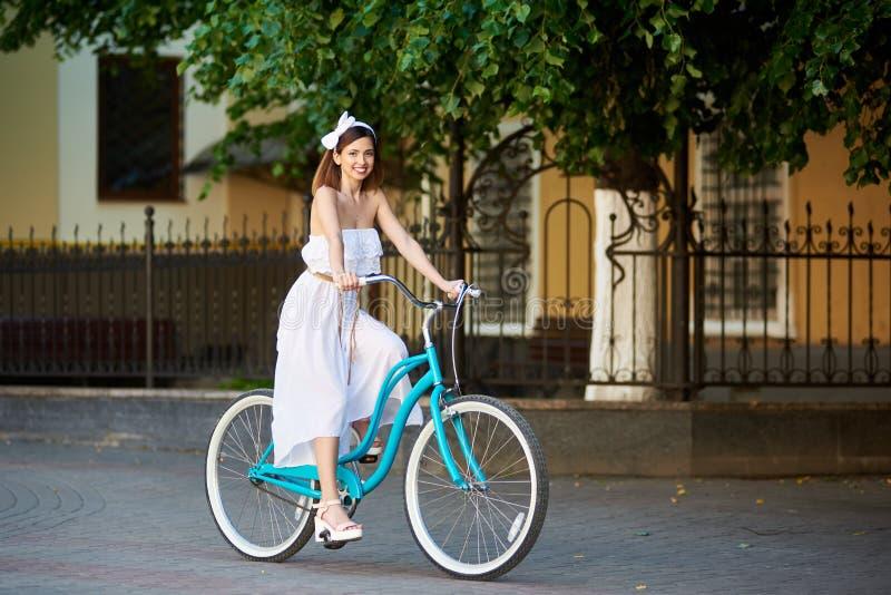 Le kvinnlign som rider en cykel på en solig stadsgata arkivfoton