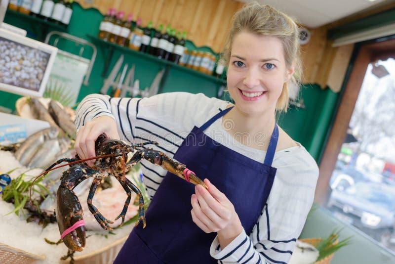 Le kvinnlign som säljer den nya fisken på marknaden royaltyfri fotografi