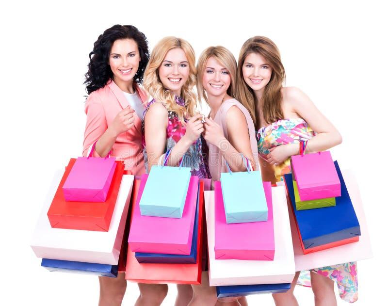 Le kvinnor med flerfärgade shoppingpåsar arkivbilder