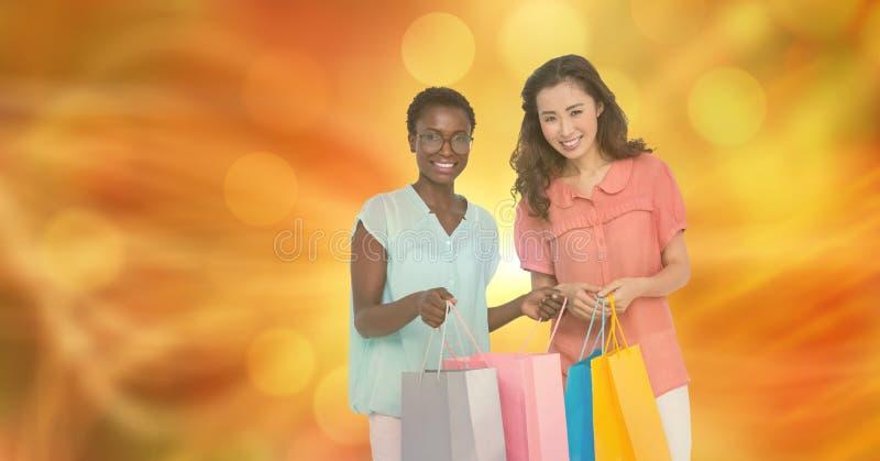 Le kvinnor med shoppingpåsar över suddighetsbakgrund arkivfoton