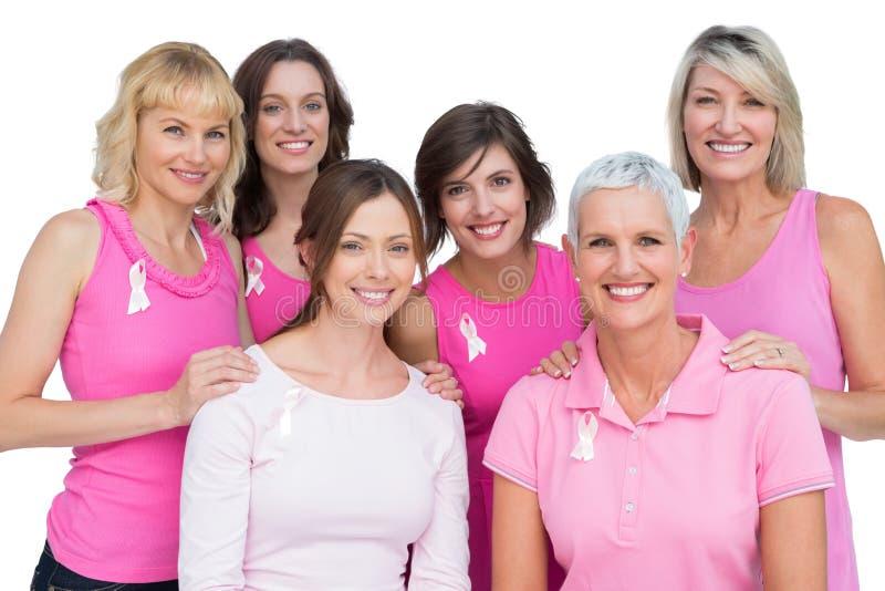 Le kvinnor som poserar och bär rosa färger för bröstcancer arkivbilder