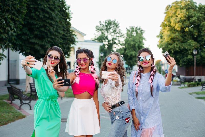 Le kvinnor som poserar och kryssar självståenden på smarta telefoner arkivbilder