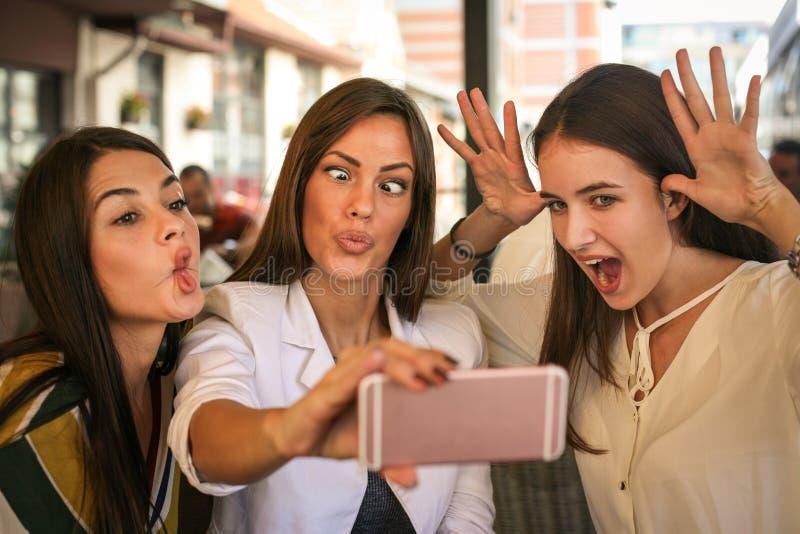 Le kvinnor som tillsammans tar selfie utomhus Flickor som gör funn royaltyfria foton