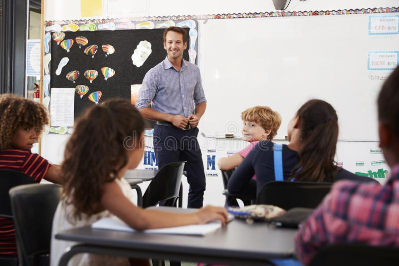 Le läraren på framdelen av grundskolagrupp arkivbild