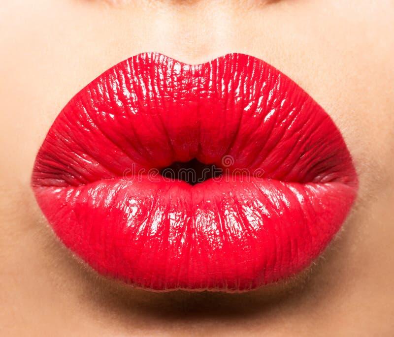 Le labbra della donna con rossetto rosso ed il bacio gesture fotografie stock