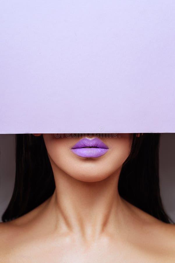 Le labbra porpora luminose esamina il foro della carta colorata fotografie stock