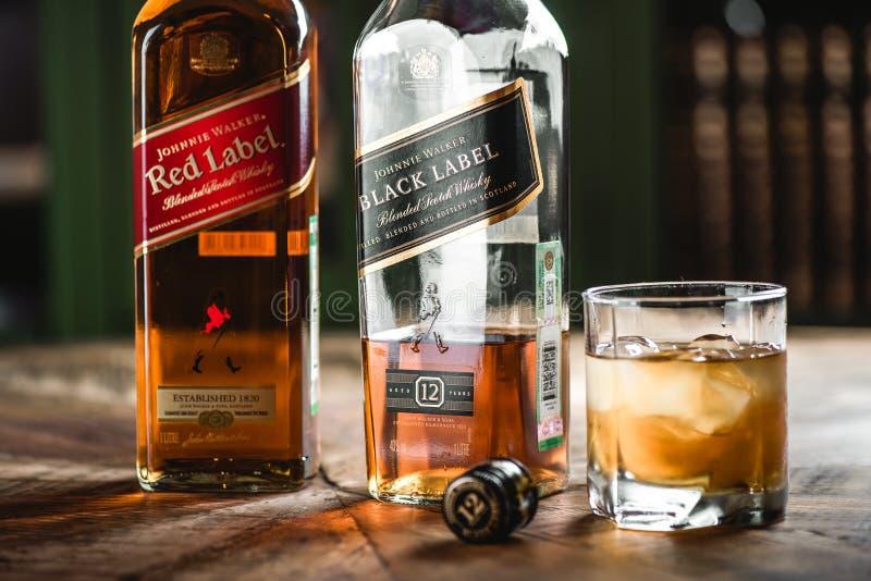 Le label rouge et les bouteilles et le verre de whiskey noirs de label avec de la glace mettent bas image stock