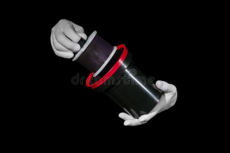 Le laboratoire, mains dans les gants blancs tiennent un noir et un film, chambre noire, developmen photos stock