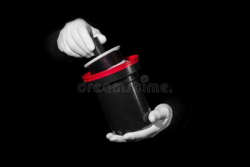 Le laboratoire, mains dans les gants blancs tiennent un noir et un film, chambre noire, developmen photos libres de droits