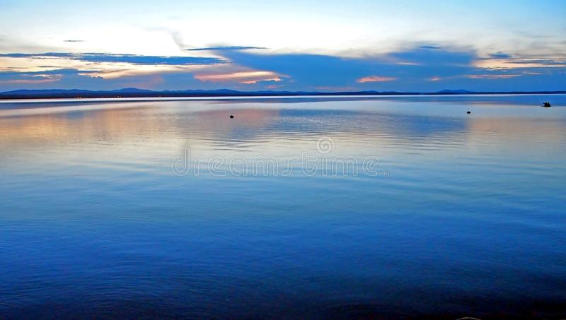 Le lac reflète le ciel bleu de coucher du soleil avec les nuages fumeux légers au-dessus de l'horizon photo stock