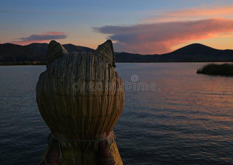 Le Lac Titicaca à la vue de coucher du soleil du Totora Reed Boat avec la proue formée par puma, Puno, Pérou photo libre de droits