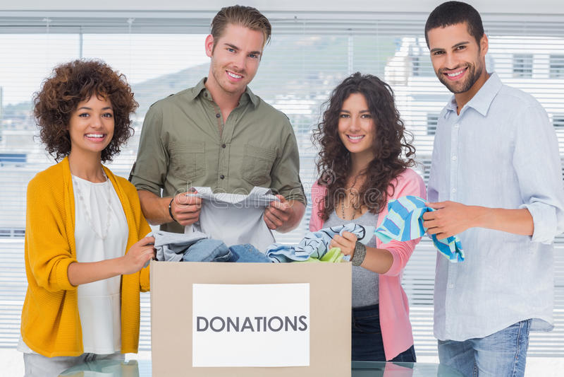 Le laget av volontärer som ut tar kläder från en donation bo royaltyfri fotografi