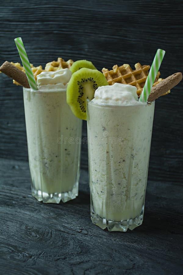 Le lait de poule avec le kiwi, la crème glacée et la crème fouettée, guimauves, biscuits, gaufres, a servi dans une tasse en verr photo libre de droits