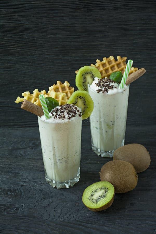Le lait de poule avec le kiwi, la crème glacée et la crème fouettée, guimauves, biscuits, gaufres, a servi dans une tasse en verr photos stock