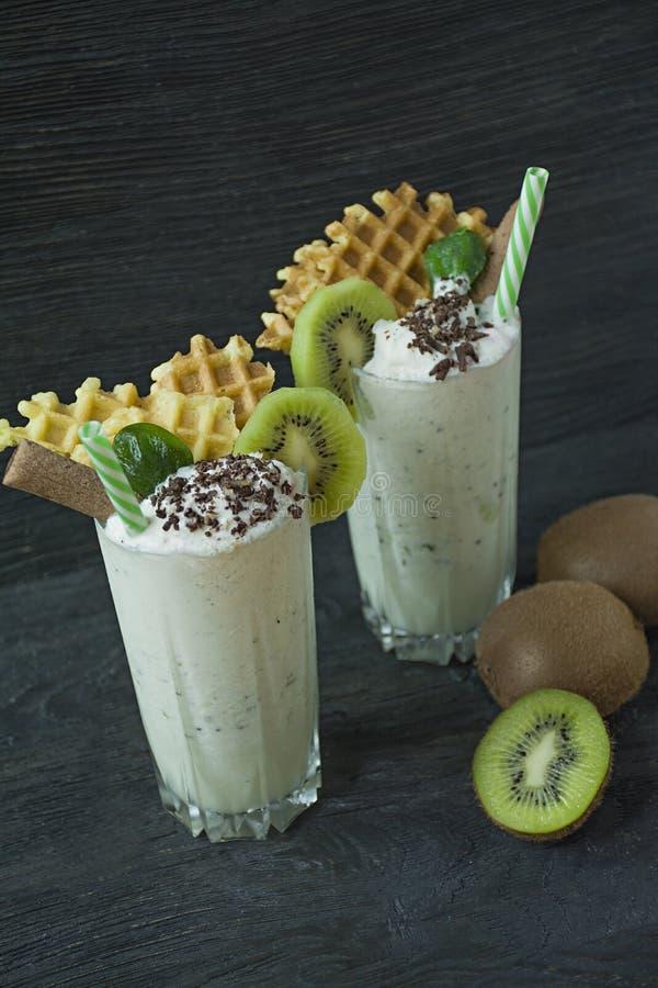Le lait de poule avec le kiwi, la crème glacée et la crème fouettée, guimauves, biscuits, gaufres, a servi dans une tasse en verr image libre de droits