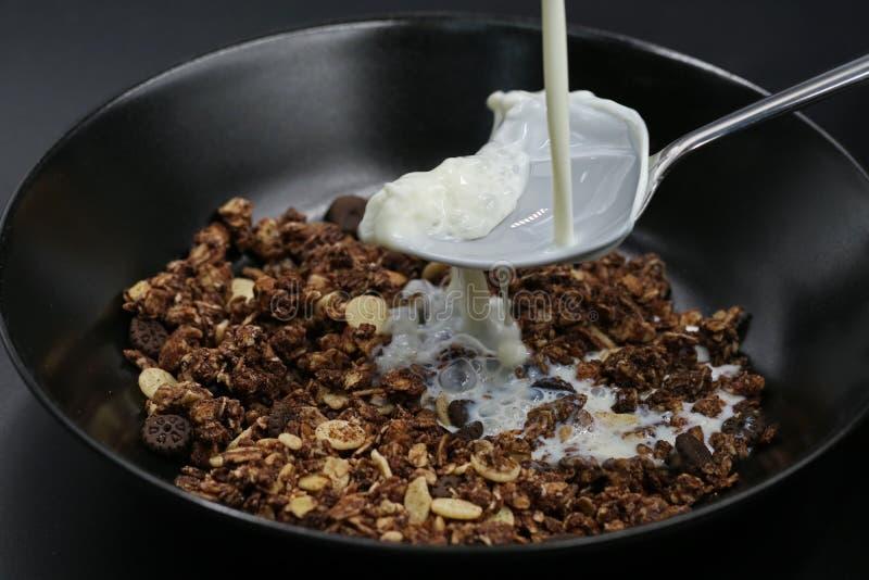 Le lait entre sur la cuillère dans le muesli de chocolat, céréales photographie stock