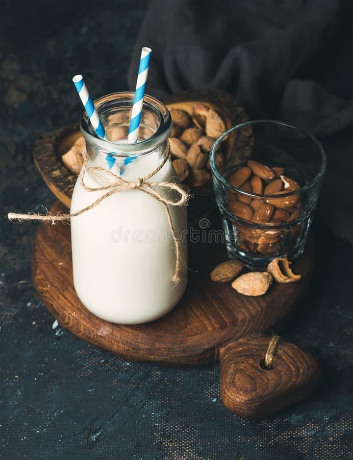 Le lait frais d'amande dans la bouteille en verre a servi avec des amandes images libres de droits