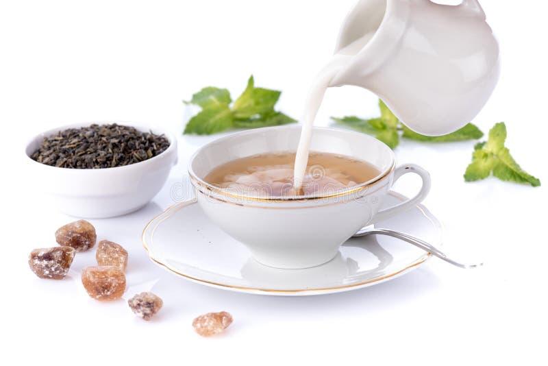 Le lait s'est renversé dedans une tasse de thé image stock