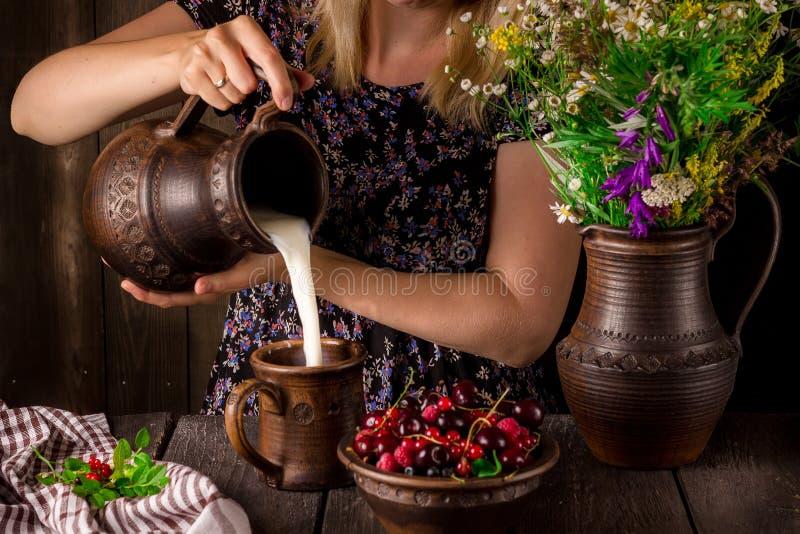 Le lait se renversant de fille d'une cruche dans une tasse et une cuvette avec des baies sur une table en bois Cruche avec des fl photo libre de droits