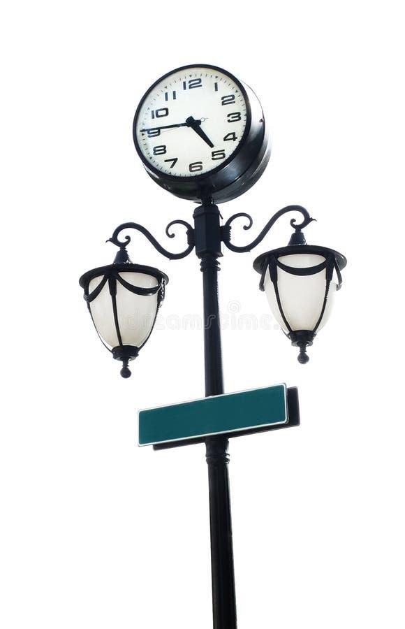Le lampadaire noir avec l'horloge ronde et la copie verte espacent le signage photographie stock
