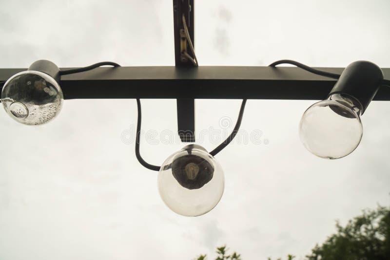 Le lampadine del giro d'annata hanno decorato il giardino all'aperto a casa immagini stock libere da diritti