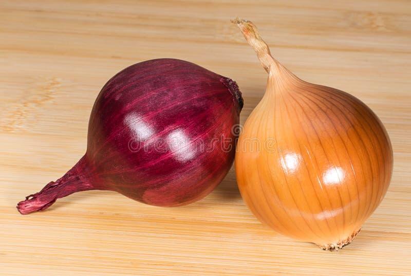 Le lampadine porpora e marroni della cipolla sulla cucina imbarcano fotografia stock