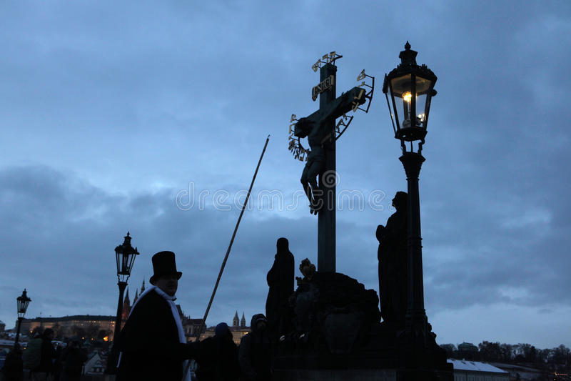 Le Lamplighter allume une lumière de gaz de rue chez Charles Bridge dans P images libres de droits