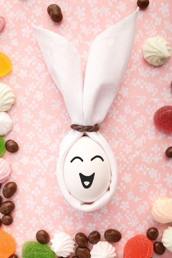 Le lapin de Pâques fait main des oeufs et des serviettes de tissu se trouve autour des bonbons image stock