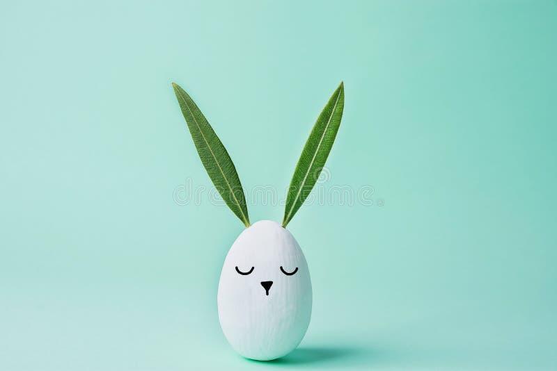 Le lapin peint par blanc décoratif d'oeuf de pâques avec Kawaii mignon tiré font face Feuilles de vert comme oreilles Fond en pas photographie stock libre de droits