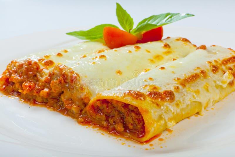 Le lasagne al forno italiane rotolano su un piatto bianco immagine stock