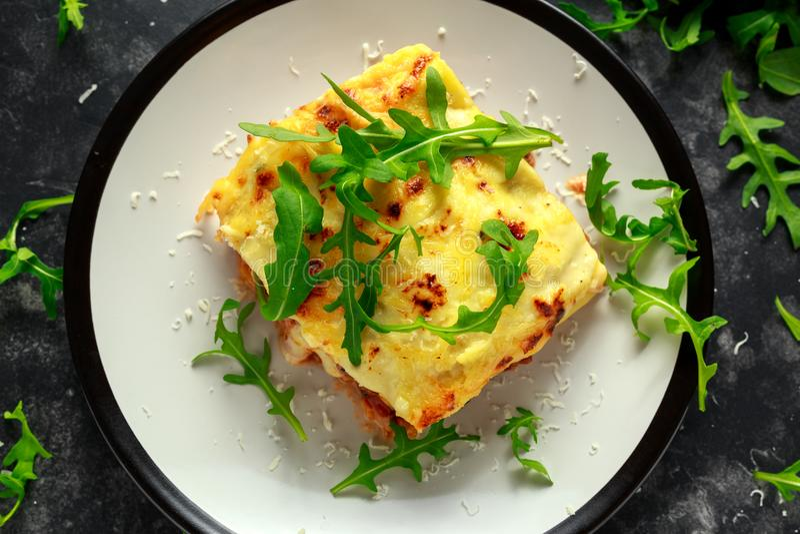 Le lasagne fait maison avec du boeuf haché Bolonais et le bechamel sauce ont complété l'arugula sauvage, parmesan image stock