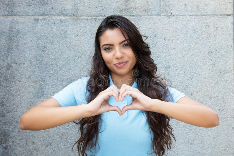 Le latin - förälskad visninghjärta för amerikansk kvinna med händer arkivbild