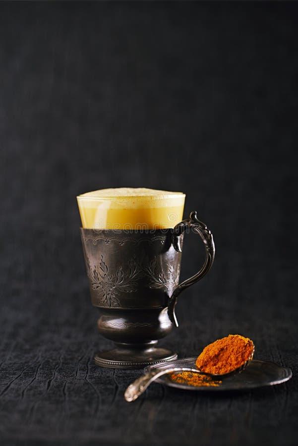 Le latte de safran des indes ou le lait d'or avec le bâton et l'épice de cannelle se mélangent photos libres de droits