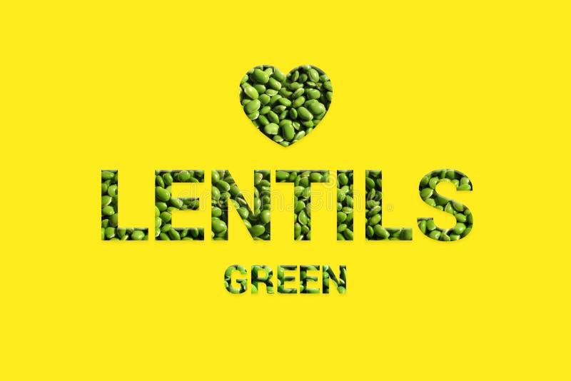 Le lenticchie verdi strutturano il testo con forma del cuore su fondo giallo fotografia stock libera da diritti