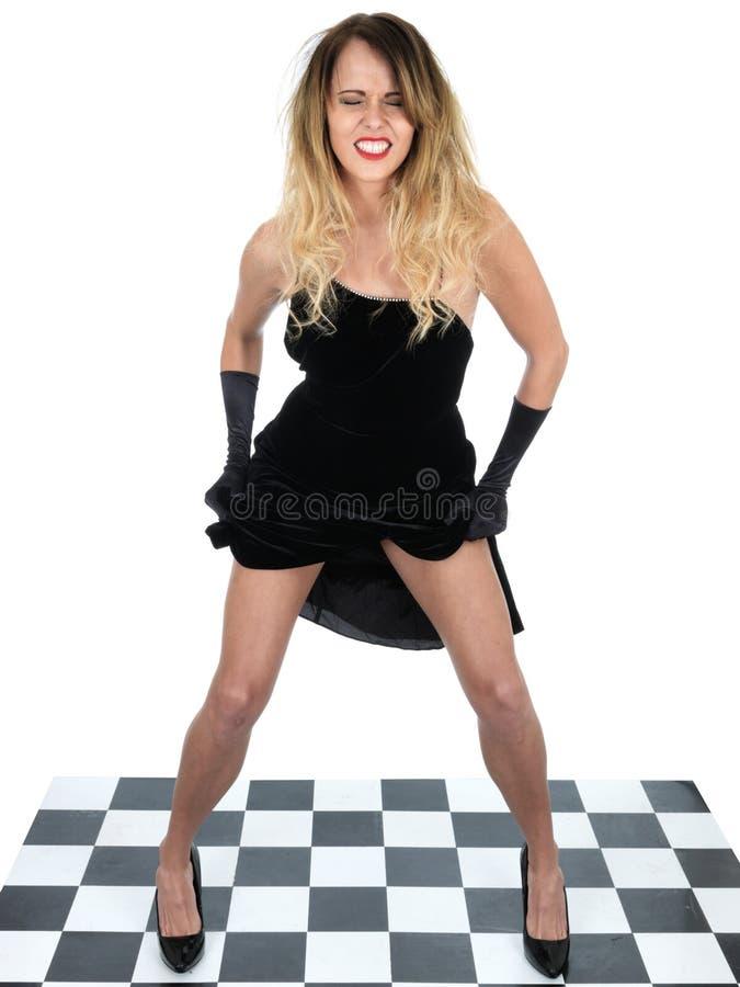 Le levage heureux de danse de jeune femme son s'habillent  photographie stock