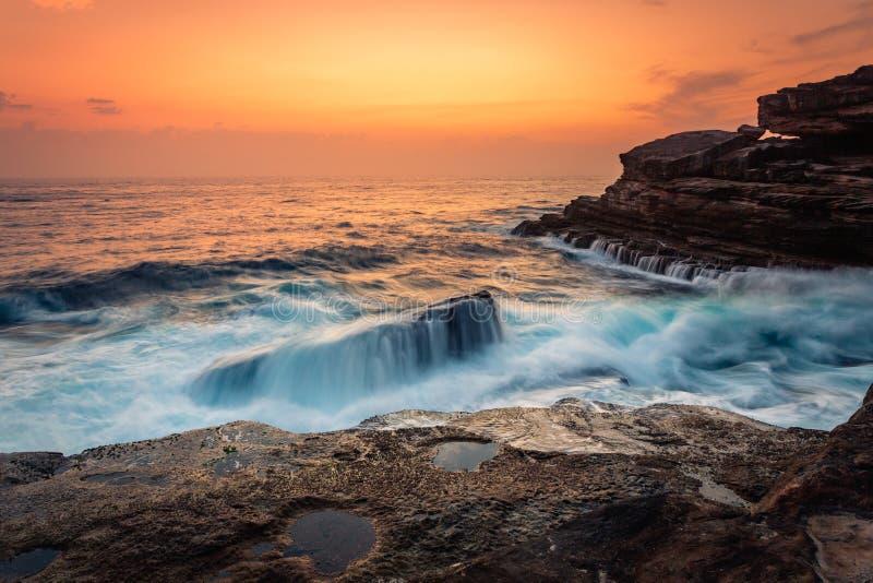 Le lever de soleil et les vagues de stupéfaction se brisent au-dessus des roches sur la côte de Sydney image stock