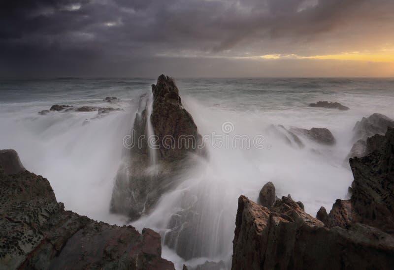 Le lever de soleil orageux et les vagues se brisent au-dessus des piles de mer photographie stock