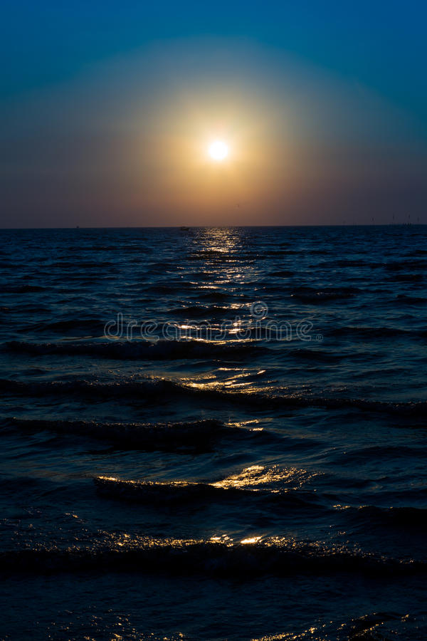Le lever de soleil sur le ciel bleu et la mer foncée pendant le matin naissent photos libres de droits