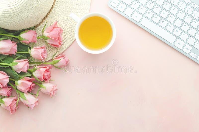 Le lieu de travail de la femme de vue supérieure avec le bouquet des roses roses sur une table rose, la tasse de thé et un chapea photos stock