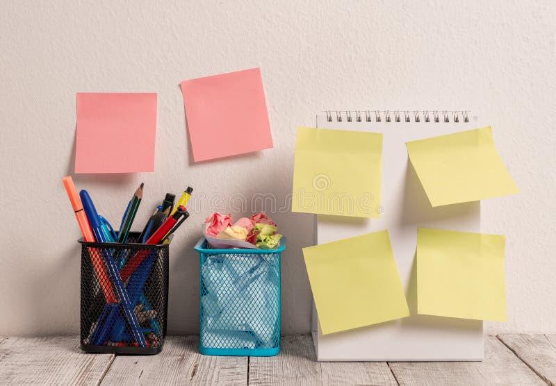 Le lieu de travail ordonn? avec 6 notes color?es vides de protection de b?ton a mis dessus le mur blanc et le carnet de notes ? s image libre de droits