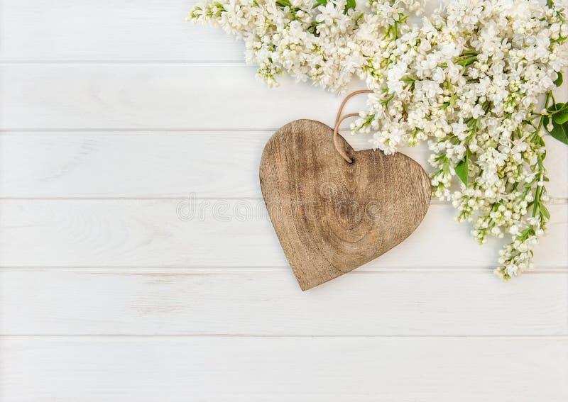 Le lilas blanc fleurit le coeur en bois photo libre de droits