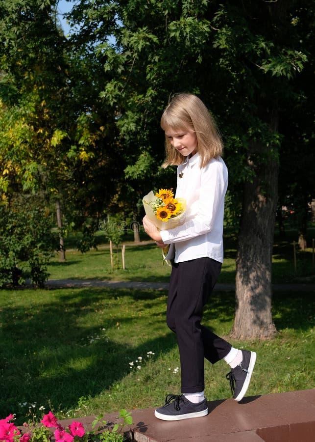 Le lilla flickan går och rymmer en bukett av solrosor arkivfoto