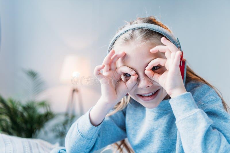 Le lilla flickan i hörlurar som visar det binokulära tecknet arkivbilder