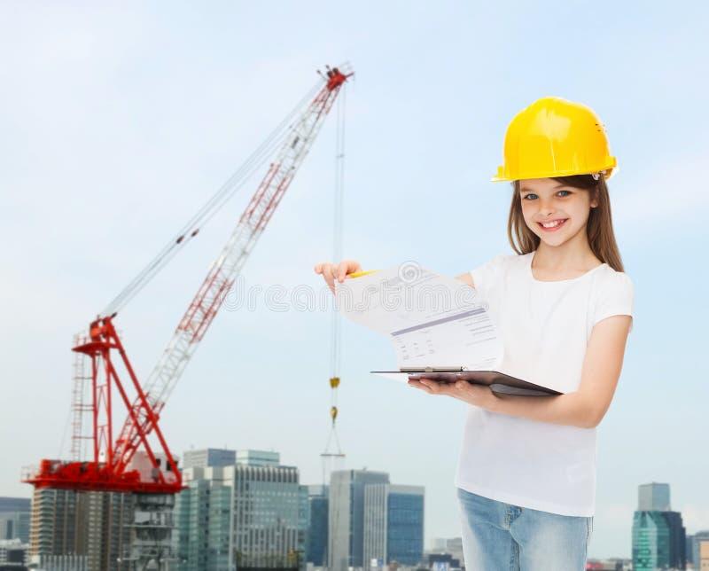 Le lilla flickan i hardhat med skrivplattan royaltyfri bild