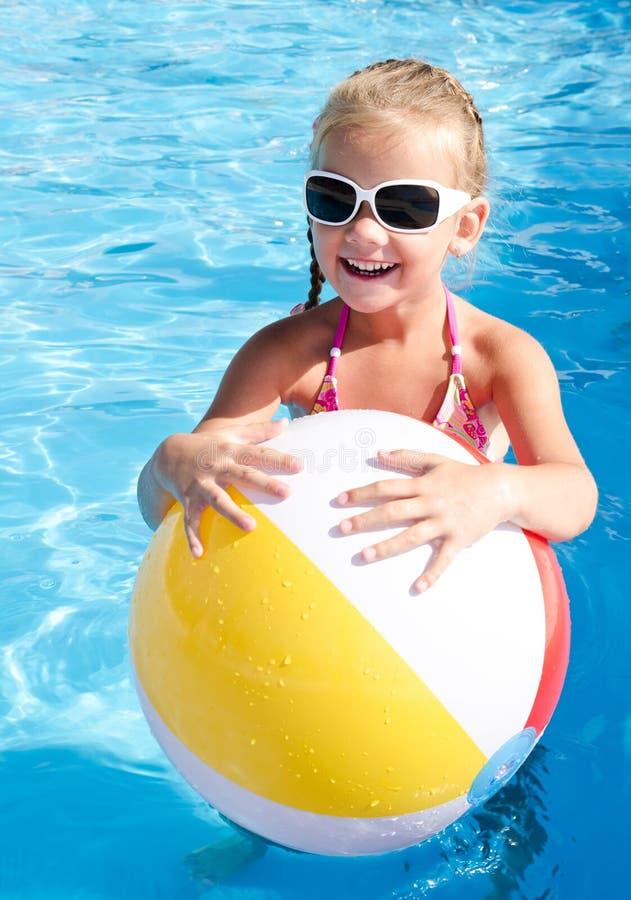 Le lilla flickan med bollen i simbassäng arkivfoto