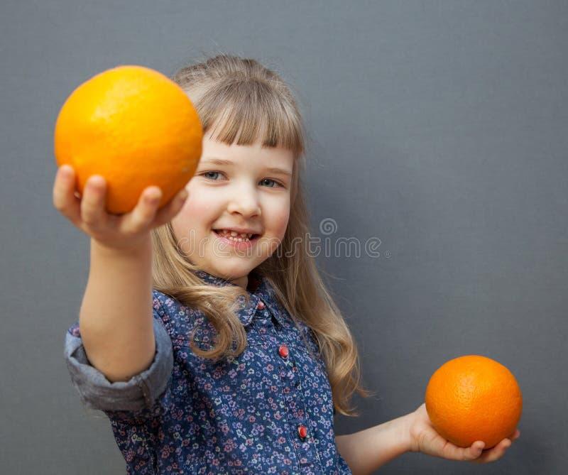 Le lilla flickan med den stora apelsinen royaltyfri bild