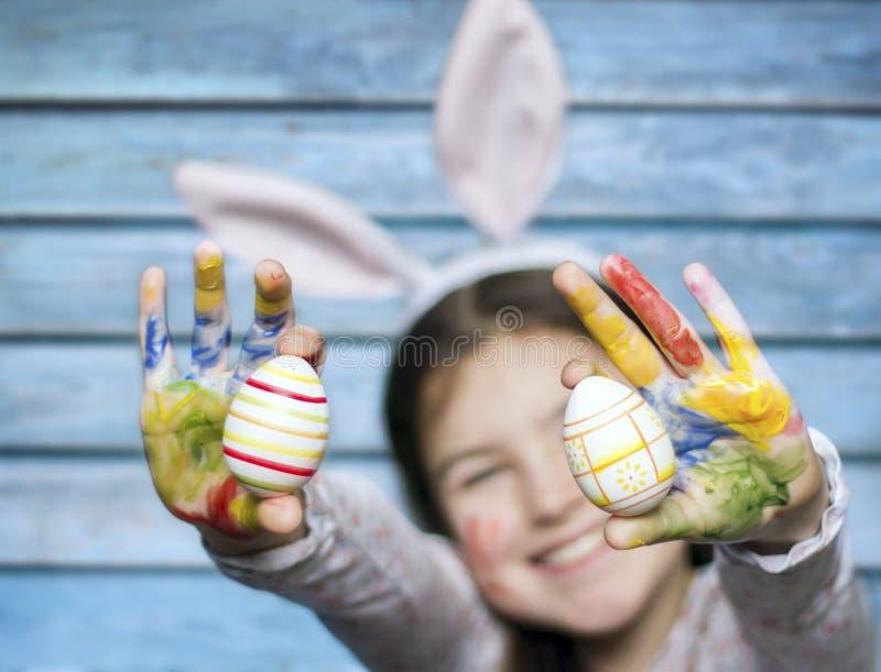 Le lilla flickan med kulöra easter ägg arkivfoton
