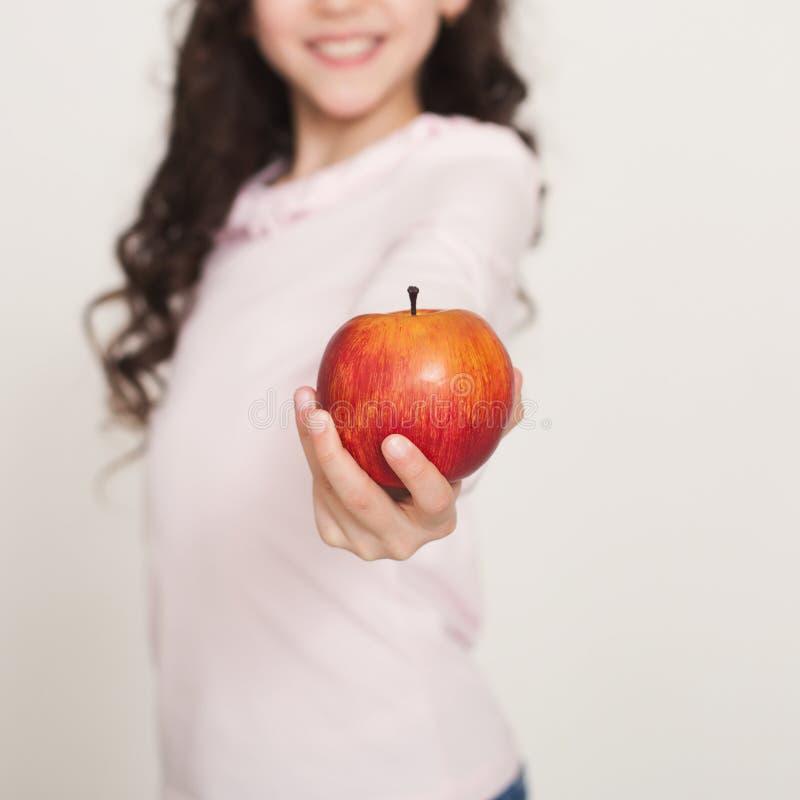 Le lilla flickan som erbjuder det röda äpplet arkivfoton